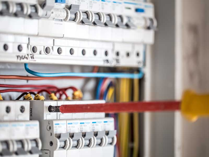 Staff member checking fuse box as part of an electrical installation condition report (EICR).